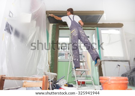 Thirty Years Old Manual Worker With Wall Plastering Tools Inside A House.  Plasterer Renovating Indoor