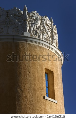 This Adobe tower with its very decorative mantel rises into the rich blue skies of Santa Fe New Mexico. The adobe wall textures are emphasized by the warm sunrise and clear blue sky. - stock photo