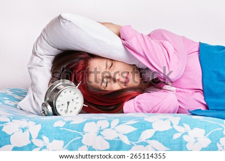 This alarm really annoys me. Young girl in bed with a pillow covering her ears due to alarm ringing - stock photo