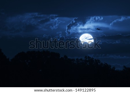 This big, bright moon illuminates the clouds and the night time sky as well as a commercial jet airliner on approach. - stock photo