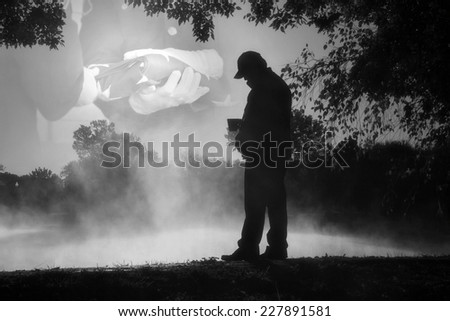 This black and white photo illustration shows an adult male reflecting on past military service and lost companions on Veteran's Day or Memorial Day. - stock photo