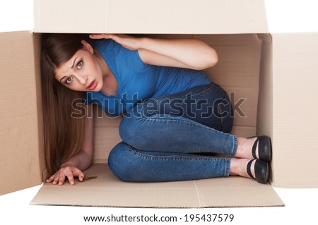 This box is too small. Shocked young woman looking at camera while sitting in a cardboard box - stock photo
