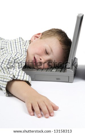This boy has had too much schoolwork and has fallen asleep on his laptop. - stock photo