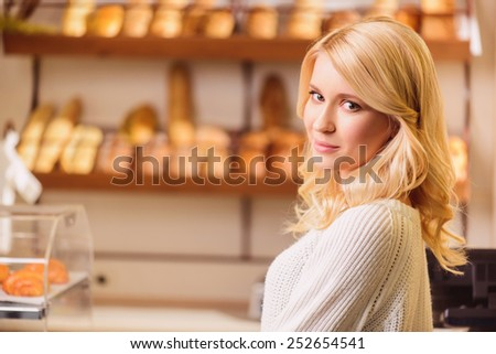 This bread is amazing. Attractive young blonde woman buying some bread in a bakery while standing against rows of fresh baked bread  - stock photo