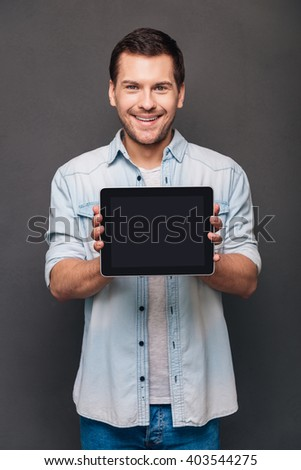 This can help you! Cheerful young man shoving his digital tablet with copy space and looking at camera with smile while standing against grey background - stock photo