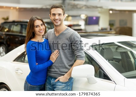 This car is exactly what we want. Beautiful young couple standing at the car dealership and making their decision - stock photo