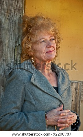 This Caucasian woman is in a thoughtful pose, wearing professional clothing in a rustic setting.  She has strawberry blond hair and is in her fifties.  Vertical and wearing a gray blazer.