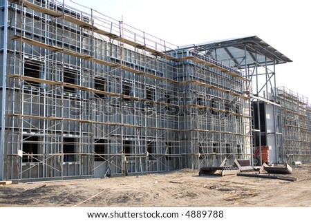 This commercial building has tilt-up concrete walls surfaced with metal studs and a sheath to be applied by workmen on the scaffolding surrounding the building - stock photo