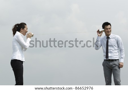 This conceptual image is about communication. Asian Business man and woman using Tin Can Phone.