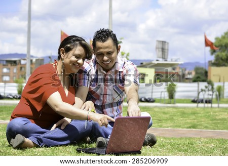 This couple are line down at the park, they are smiling - stock photo