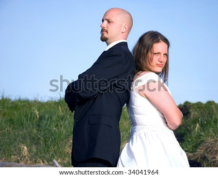 This couple in their wedding clothes are fighting and having a argument, giving the cold shoulder. - stock photo