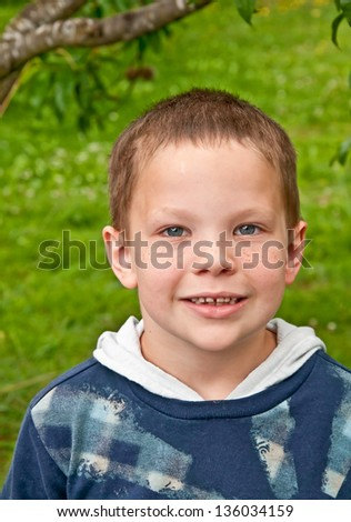 This cute little 8 year old Caucasian boy is smiling outdoors.  He is wearing a plaid type shirt, has blue eyes and freckles.  It's a head and shoulders shot, front facing. - stock photo