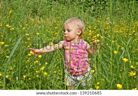 This cute toddler girl is 2 years old and playing and learning in the long grass with buttercup flowers in the field.  She is Caucasian with short blond hair, in a rural lifestyle photo. - stock photo