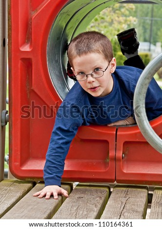 This cute 8 year old Caucasian boy is playing on playground equipment in a tunnel.  He has glasses, freckles, very short hair and wearing a long sleeved blue shirt. - stock photo