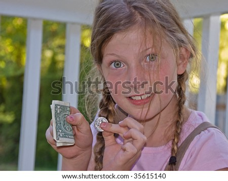 This cute 8 year old girl is holding her allowance for chores done. - stock photo
