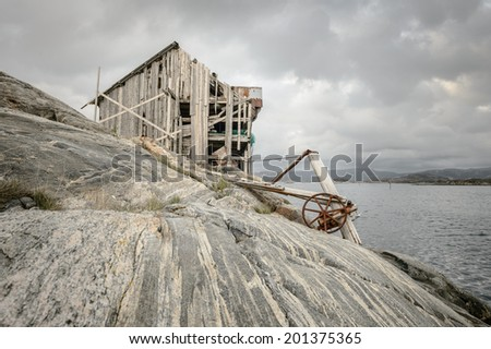 This derelict structure, now abandoned to the elements on a tiny rock outcrop off the Norwegian coast, used to be a shop and rest stop for boats carrying freight up and down the coast. - stock photo