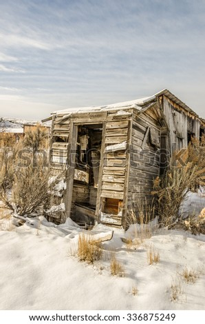 This dilapidated outhouse would not be standing if it weren't for the building behind it! - stock photo