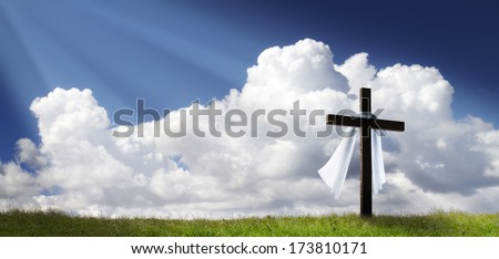 This dramatic Easter Morning Sunrise panorama with blue sky, bright clouds, sunbeams, and large cross on a grass covered hill makes a great banner cover for print or web. - stock photo