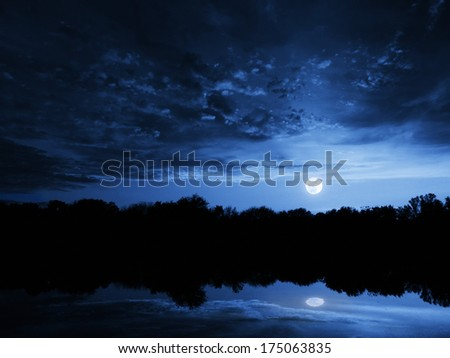 This dramatic moon rise in a deep blue night time sky is accented by highlighted clouds and beautiful, calm lake reflection. - stock photo