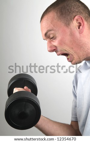 This dumbbell is far too heavy for this man. - stock photo
