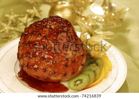 This glazed oven roasted Ham with cloves, Golden berries and Kiwi fruit is a modern rendering of a traditional Brazilian Christmas dish. - stock photo