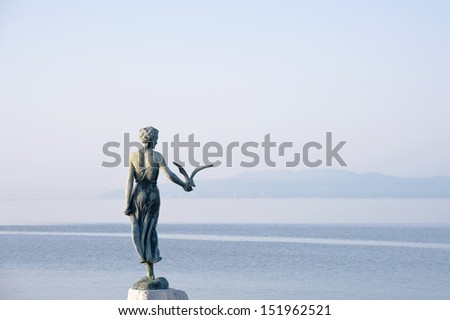 This historic statue on the Adriatic coast is a symbol of touristic town Opatija in Croatia. Lady with a seagull monument Opatija Croatia - stock photo