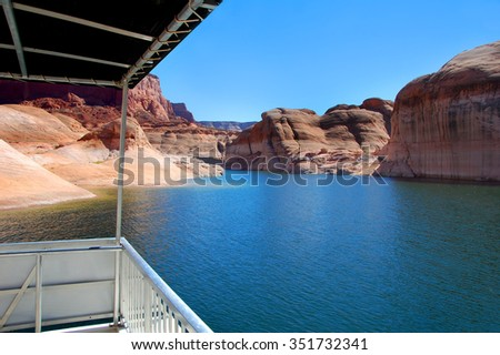 This houseboat has a view!  Beautiful sandstone rocks and steep cliffs tower over Lake Powell and its waterway. - stock photo