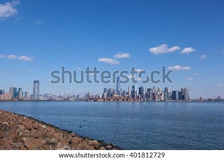 This image contains views of Jersey City and Manhattan, from Liberty State Park. You can see Goldman Sachs Tower, 432 Park, Empire State Building, Freedom Tower, Ellis Island, and the Brooklyn Bridge. - stock photo