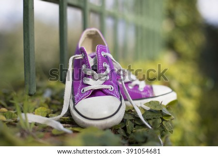 This image expresses the freedom and carefree children; concepts represented from the outdoors where the photo was taken and the string untied. / outdoor portrait of a little girl sneakers shoes - stock photo