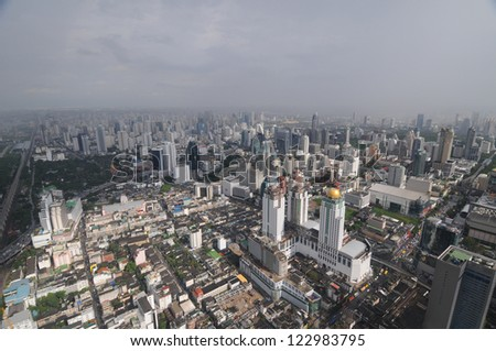 This is a bird's eye panorama of Bangkok, Thailand. The sun closed buildings in the foreground, in the last part of the city it is raining. - stock photo