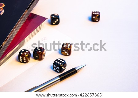 This is a casual set of dice displayed on a book. The purpose is to visualize traditional board games and roleplaying games.