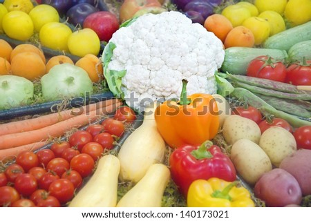 This is a circular display of various fruits and vegetables, with a white cauliflower as the center.  Tomatoes, carrots, squash, potates, apricots, apples, and peppers are in this food image. - stock photo