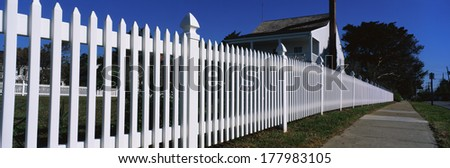 This is a close up of a white picket fence and a typical looking suburban house. We see the sidewalk that runs past it on the right hand side of the image. - stock photo
