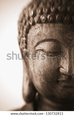 This is a close-up photograph of an antique wood carving of a sculpture of Buddha with focus on the downcast eye. The sepia image was taken with a Lensbaby and has a very shallow depth of field. - stock photo