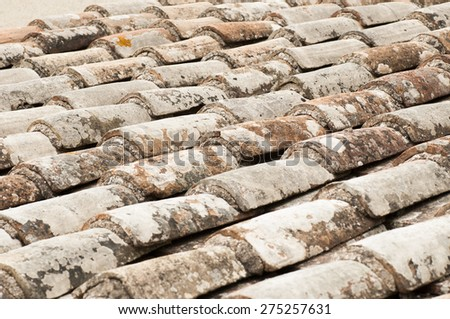 This is a close-up view of an old roof with red tile - stock photo