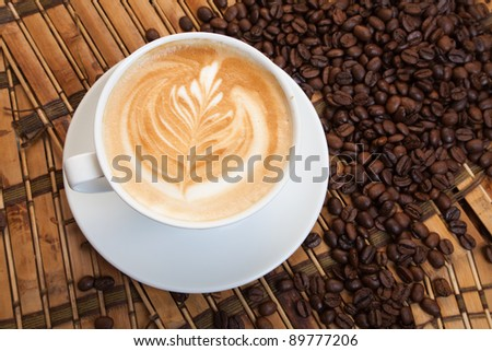 This is a cup of espresso coffee with a pattern on the foam and corn coffe on background. - stock photo