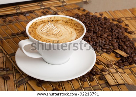 This is a cup of espresso coffee with a pattern on the foam and corn coffee on background. - stock photo