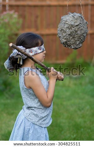 This is a girl about to whack a wasp nest pinata - stock photo