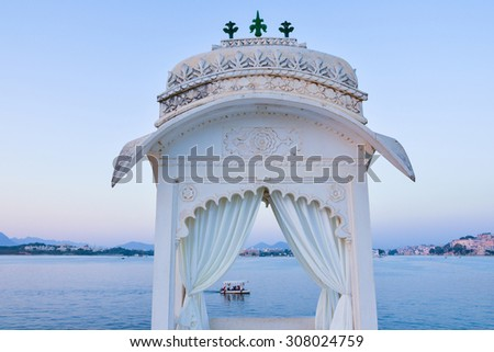 This is a horizontal, selective focus shot of a boat ride on Lake Pichola. This was shot at dusk from a viewpoint at the Island Palace in Udaipur, India. The lake shore is seen beyond.  - stock photo