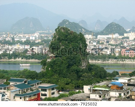 This is a jungle covered hilly peak that houses many caves and temples in the city of Guilin China.