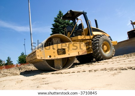 This is a large highway construction packing roller used to pack sand and aggregates before the laying of asphalt. - stock photo
