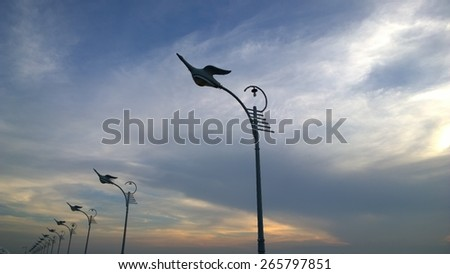 This is a line street lamp on the sky near the sea - stock photo
