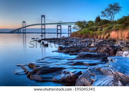 This is a long exposure HDR of the illuminated Newport bridge from Taylor's Point near Jamestown, Rhode Island, USA. It was taken at sunrise with a rocky seascape in the foreground. - stock photo