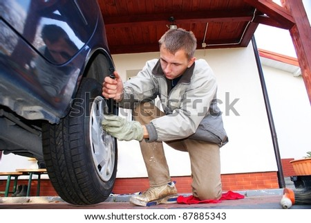 This is a man changing the wheel in the car