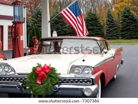 this is a mid 1950s car at a gasoline service station with a wreath on the front of the grill. - stock photo