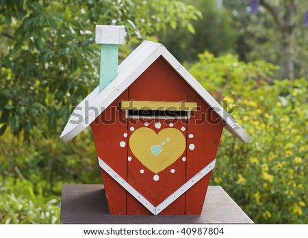 This is a model house used as a mail box.  The house is rustic and colorful.  On the front is a big heart. The background is countryside.