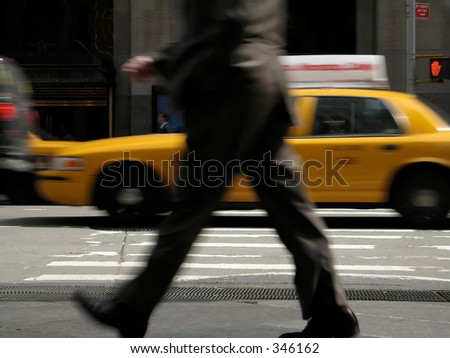 This is a motion blur of a business man walking down the street with a moving cab in the background.