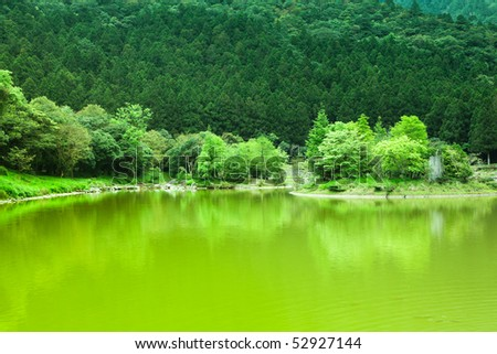 This is a mountain pond with green trees - stock photo