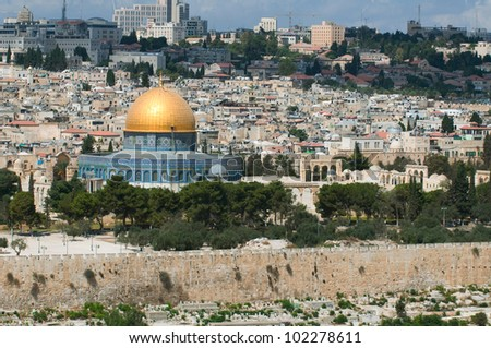 This is a panorama of Jerusalem city. Photo contains ancient buildings, domes and modern architecture on the background.