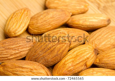 This is a photo of some almonds layed out on a wooden cutting board.